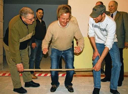 """Die Einspringetradition für die """"Neuen"""" - Helge Thomsen springt über den Stab, der von den beiden Ältermännern gehalten wird Foto: Düvell-Veen"""